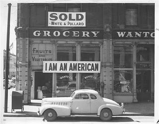 "A large sign reading ""I am an American"" placed in the window of a store, at 13th and Franklin streets, on December 8, the day after Pearl Harbor. The store was closed following orders to persons of Japanese descent to evacuate from certain West Coast areas. The owner, a University of California graduate, will be housed with hundreds of evacuees in War Relocation Authority centers for the duration of the war."