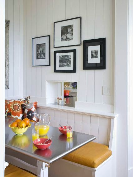 Breakfast nook in a san francisco mansion with white bench style seating with yellow cushions, a metal table, and bright flower print pillows. There are pictures on the wall in black frames.