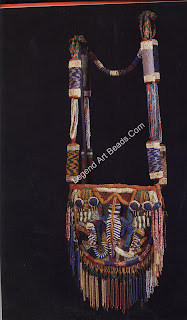 A Yoruba diviner's bag from late nine-teenth- or early twentieth-century Nigeria, used to carry ritual accessories. The six cylinders in the strap are bead-covered corncobs. Height, 125.7 cm. Collection Ruth and Paul Tishman, New York