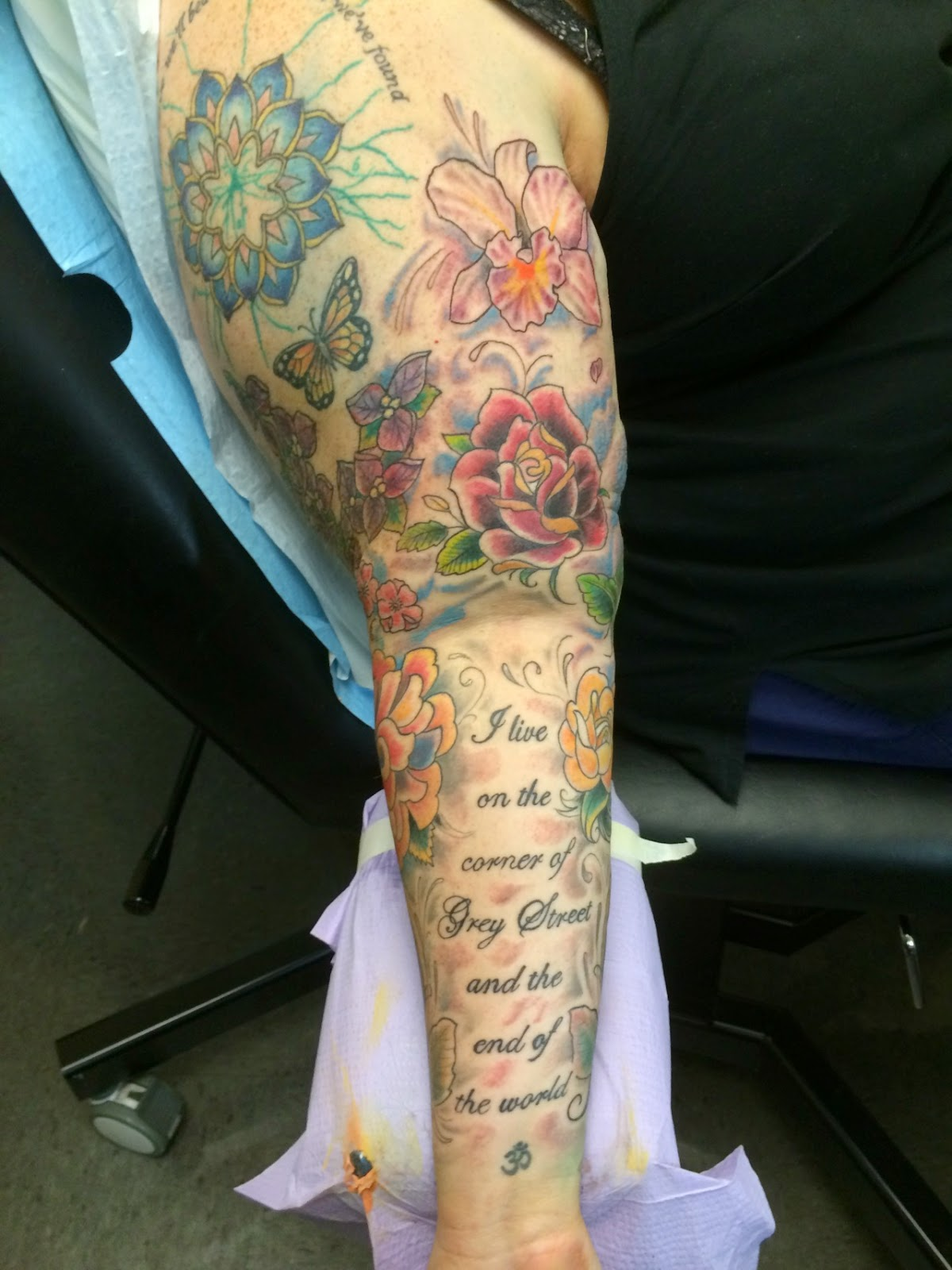 "Photograph: A tattooed arm. At top is a lotus with the words ""By love we'll beat back the pain we've found."" Below are a butterfly and a sprig of bougainvillea. To the right of that are an orchid and a red. Below these is the phrase ""I live on the corner of Grey Street and the end of the world."