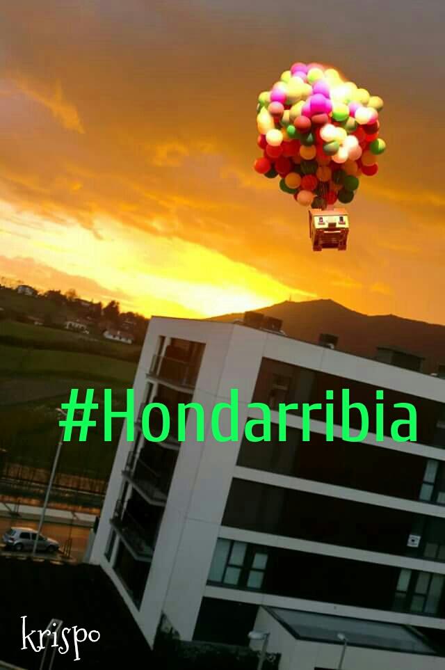 imagen de hondarribia con casa voladora y un hashtag
