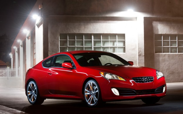 Front 3/4 view of 2011 Hyundai Genesis Coupe 3.8 R-Spec in front of warehouse at night