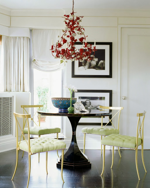 Dining room with gold chairs with mint green tufted seat cushions and a red chandelier