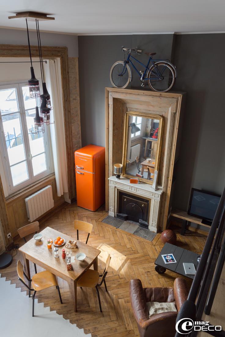 Plafonnier réalisé avec des baladeuses de chantier, table de cuisine chinée entourée de chaises d'écolier '5 Francs'