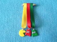 Medalla Pacman con tres cintas que portan a un comecocos y dos fantasmas
