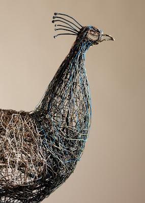 Ingeniosa escultura de ave con cables de teléfono.