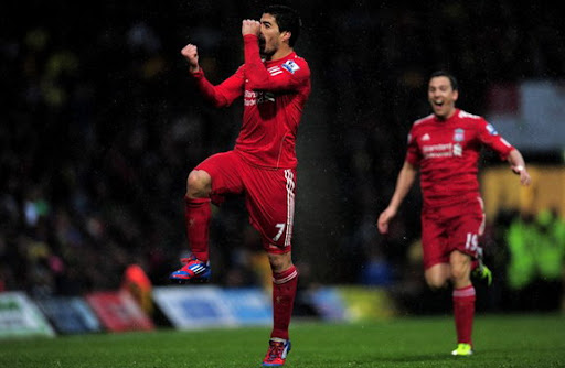 Liverpool striker Luis Suárez celebrates after scoring from 45-yard out against Norwich