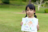 "Child holds ""Save Our Earth"" sign (Credit: Shutterstock) Click to Enlarge."