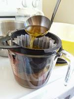 Ladling dandelion tea into coffee maker basket filter over a measuring cup.