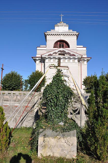 Petrykozy, krzyż żeliwny na postumencie. Krzyż jest mało widoczny - obrośnięty bluszczem. W głębi kościół parafialny p.w. św Doroty zbudowany 1791 wg projektu architekta Jana Chrystiana Kamsetzera, restaurowany w 1937. Fot. KW.