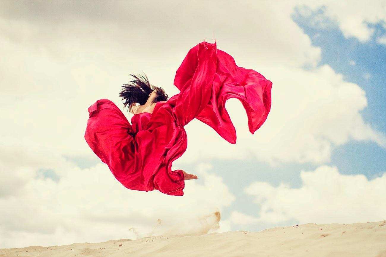 fille brune dans une longue robe rouge sautant d'une dune par Dasha Kond