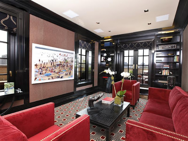 Black lacquer den with red velvet sofa chairs with nailhead trim, red and black graphic rug, black french doors and encasement windows, black and gold Roman shades, and a black built in book case