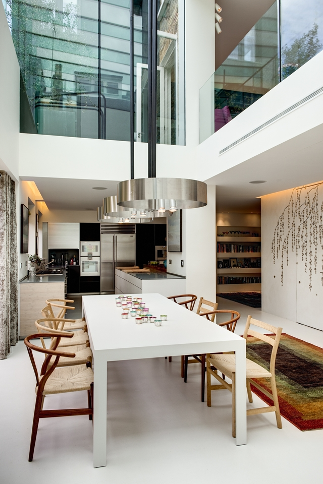 Picture of modern dining room with high ceilings and modern kitchen in the background