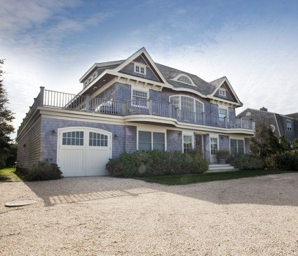 exterior of a house in the Hamptons with a small lawn and driveway made of tiny rocks