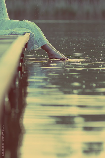 girl dipping feet in water