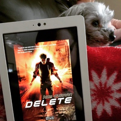 A white Kobo with Delete's cover on its screen occupies most of the shot. Murchie, a sleek grey poodle, peeks out from behind it. The cover depicts a white boy in a hoodie standing in the orange-tinged ruins of London.