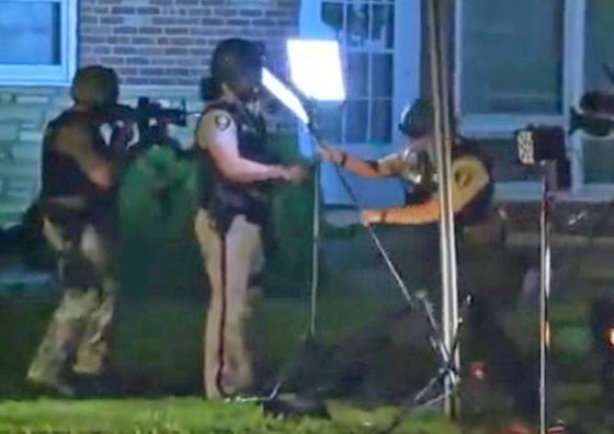 After gassing a news crew, cops point machine guns and take down their video equipment.(Screen capture from video)