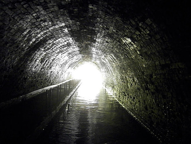 light shines at the end of a tunnel