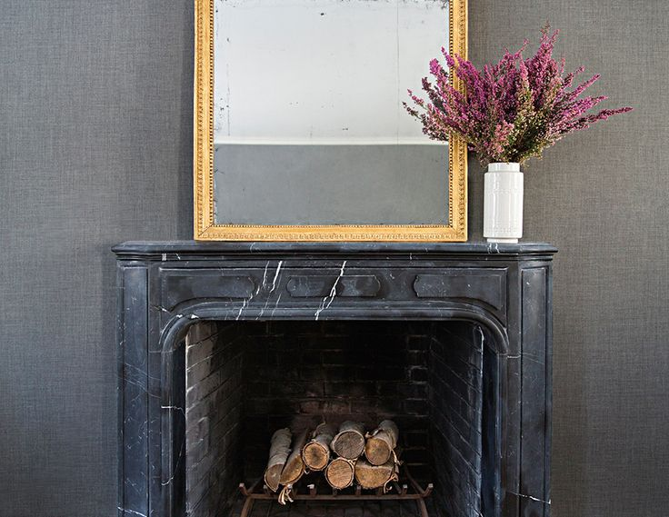 Black marble fireplace and brass mirror