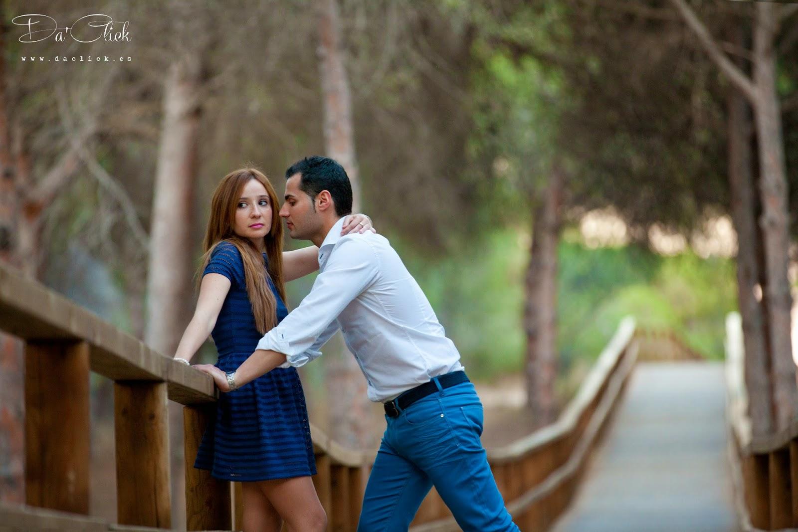 pareja en una pasarela de madera rodeada de pinos