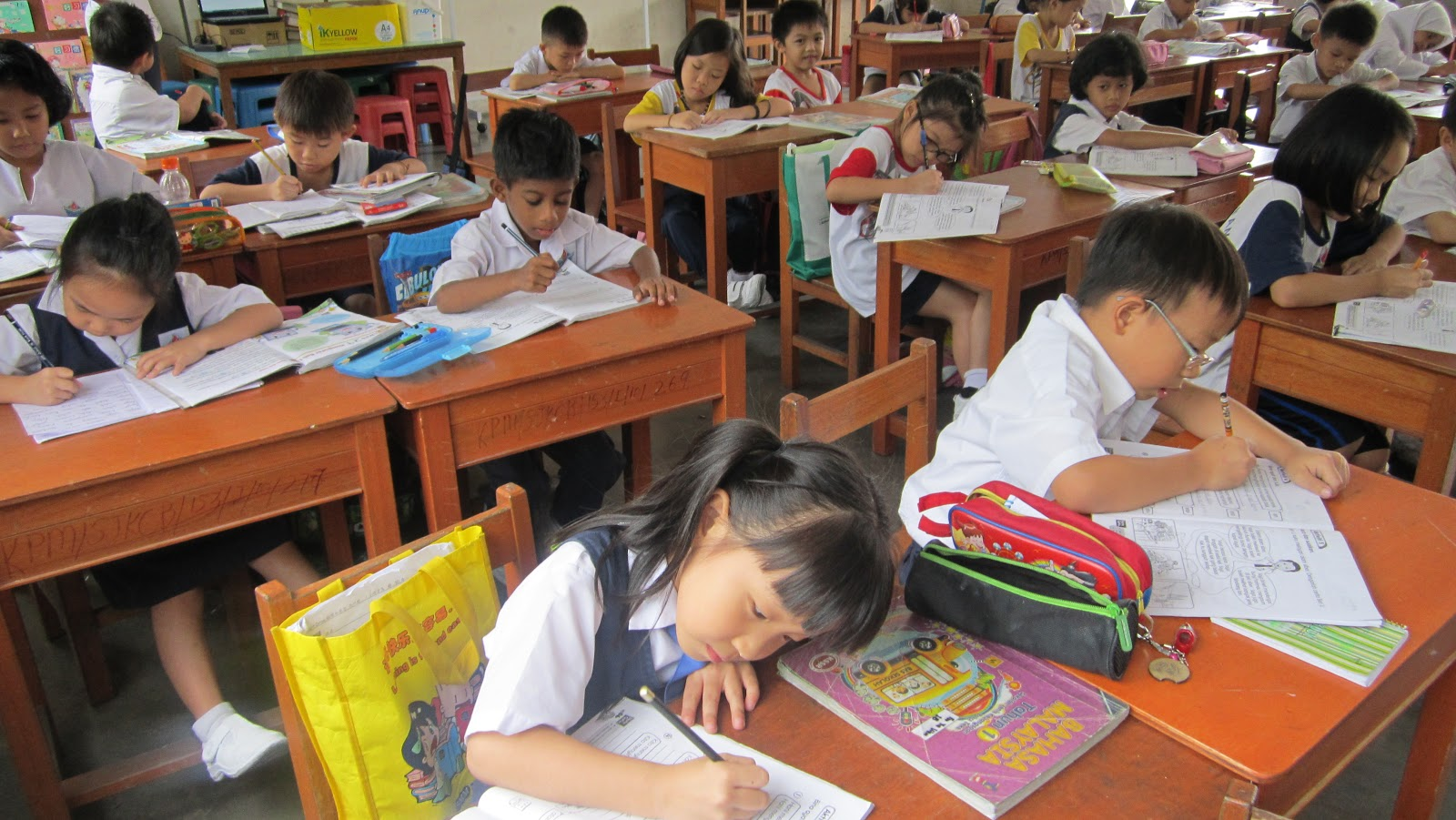 Pelajar sedang sibuk menyiapkan buku latihan.