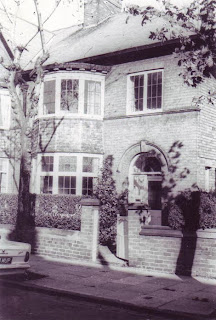 A large 1930's semi detached baywindowed house.  With a wall and hedge in front.  The shadows of trees are being cast across the front of the house, the picture was taken when the sun was very low