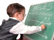 Little boy writing maths problems on a chalkboard.