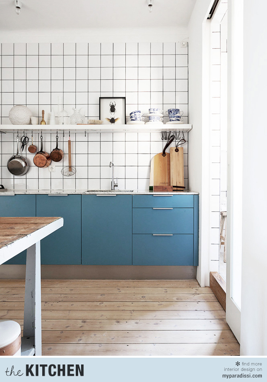 Kitchen with blue cabinetry, white tiled splashback and wooden floor.