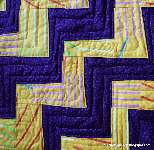Purple and gold fabrics in a rail fence pattern.