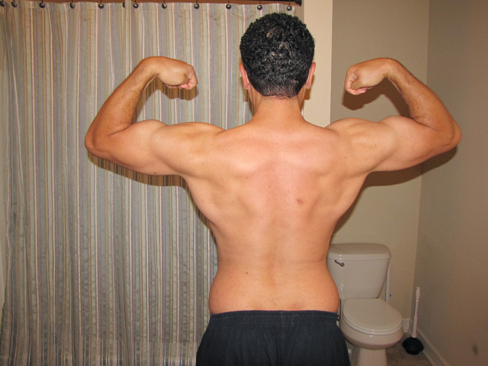Damond Nollan flexing back muscles.