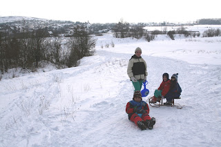 """Szöveg: """"ha lehet elmegyünk szánkózni"""". Kép: Téli vidéki táj, előtérben a három gyerek és a feleség, háttérben egy falurészlet. Minden hidegről árulkodik, és az egész család jól be van öltözve."""