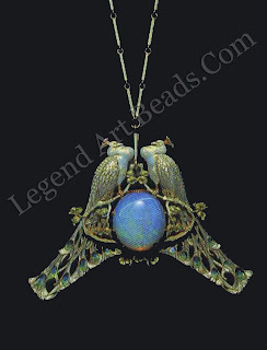A pendant of two peacocks on a prunus branch in gold and enamel, facing each other above an opal (c. 1902-03).