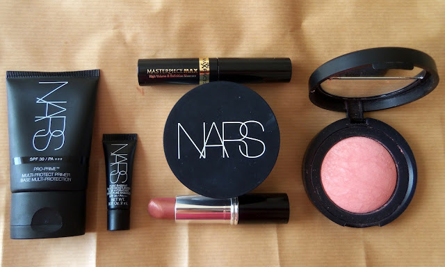 Nars Pro Prime Primer SPF 30 Nars Pure Radiant Tinted Moisturizer SPF 30 in St Moritz Nars Translucent Crystal Light Reflecting Loose Setting Powder Laura Geller Baked Blush in Bora Bora Laura Geller Double Dipped Lipstick 2-in-1 Lip Color in Caribbean Kiss (bronzy side) Max Factor Masterpiece Max Mascara in Black