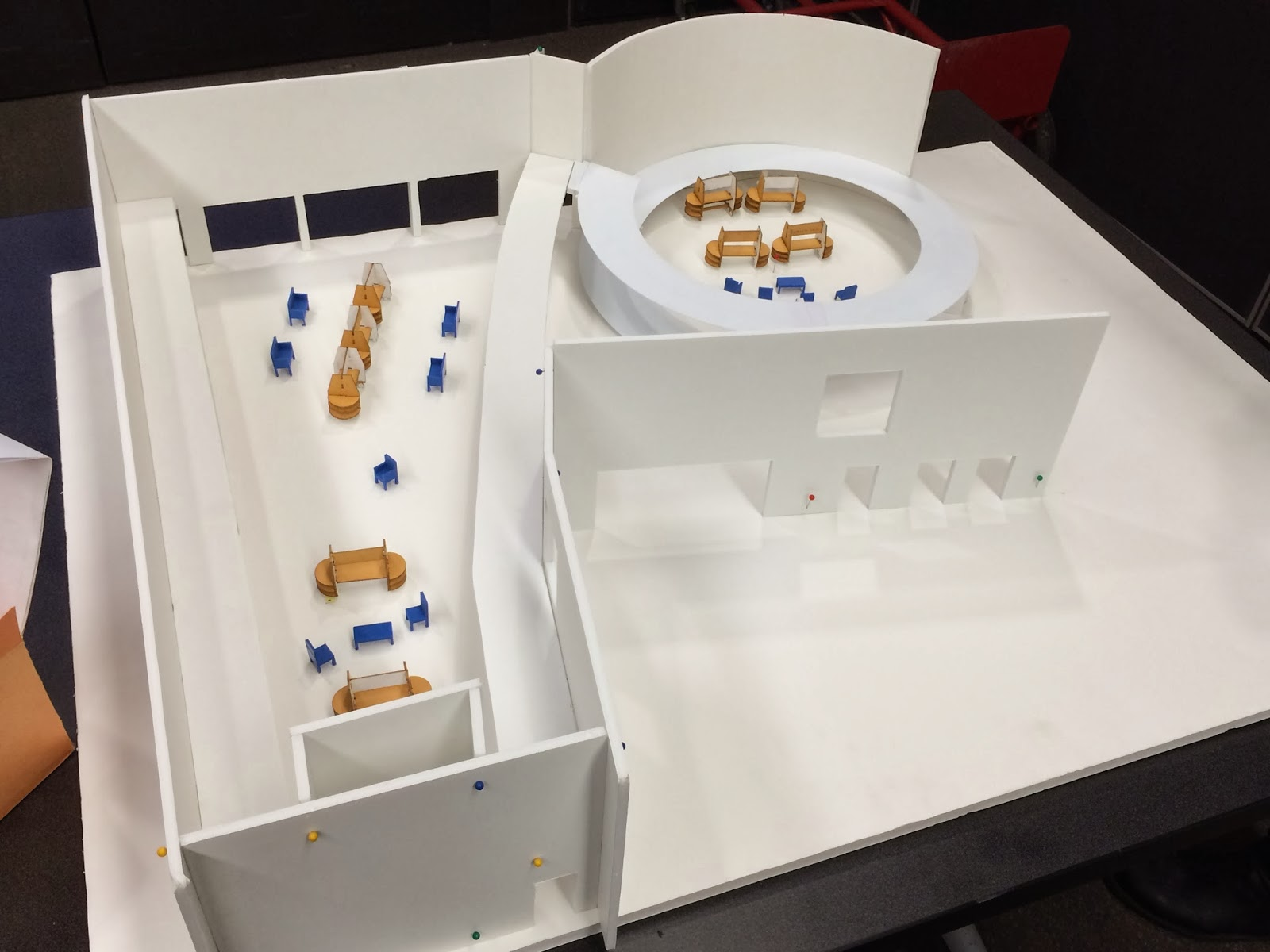 A top frontal view of the white building model shows the small exhibit displays and chairs in placeand how the layout would look.