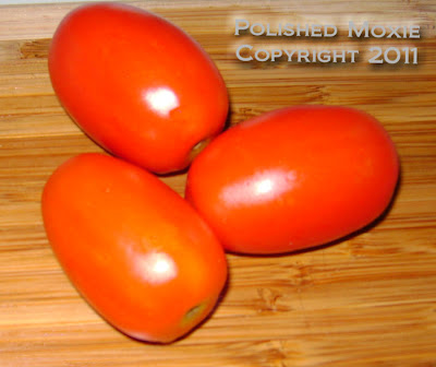 Picture of three plum tomatoes sitting on a wooden cutting board.