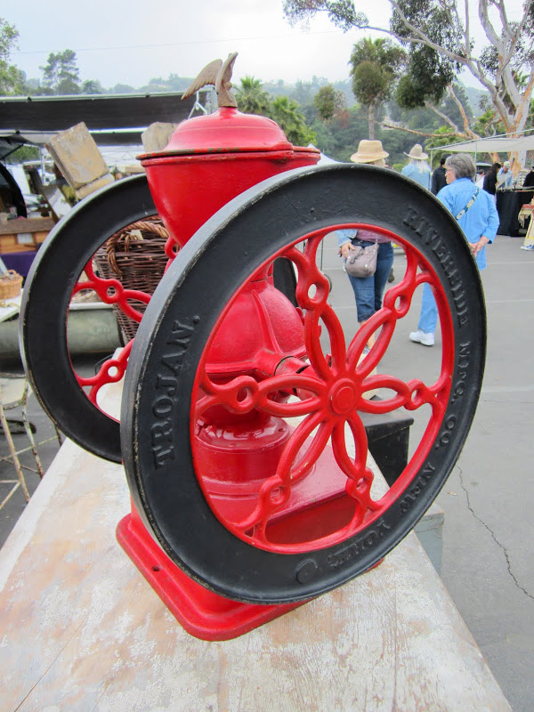 A bright red antique coffee grinder