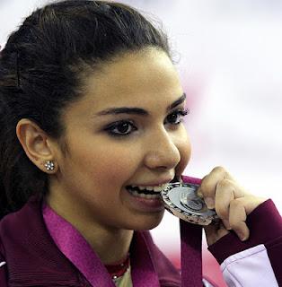 Gümüş madalya kazanan sporcunun madalyasını ısırarak poz vermesi spor müsabakalarında görmeye alışık olmadığımız bir sahne. (Zaten ben de bu fotoğrafı çok zor buldum!) Fotoğraftaki sporcu gümüş madalyasını ısırarak zafer pozu verirken çok da mutlu olmadığı gözlerinden okunuyor. Fotoğraf: Doha Stadium Plus