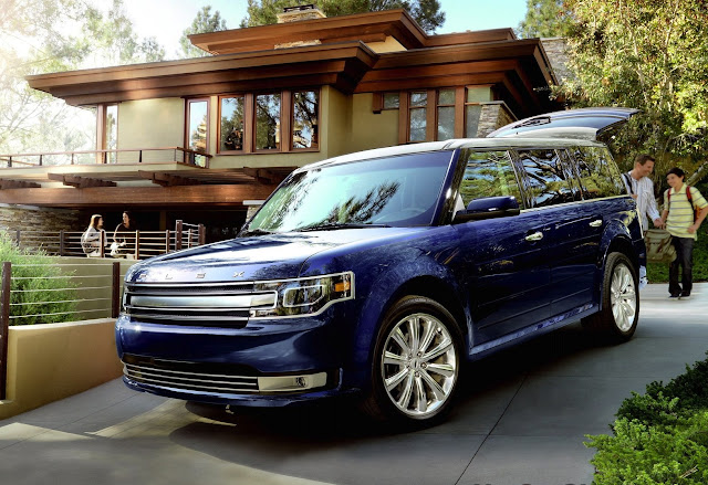 Front three-quarters view of blue 2013 Ford Flex. in suburban driveway