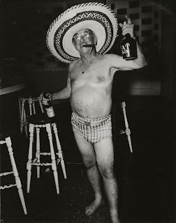 Image of American tourist, wearing plaid swim trunks and a sombrero, smoking a cigar and carrying a liquor bottle in each hand.