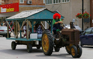 image Millbrook Ontario Fair Parade entry Tractor driven by clown pulling float past Home Hardware