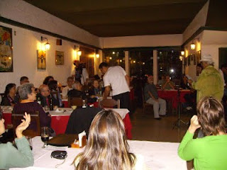 A foto mostra uma visão geral das mesas e do público presente no Salsa e Cebolinha, na Lapa