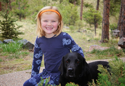 Young Claire smiles sitting next to Bluebell (black Lab) in the woods with trees in the background.