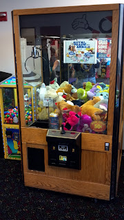 claw crane game filled with plush toys