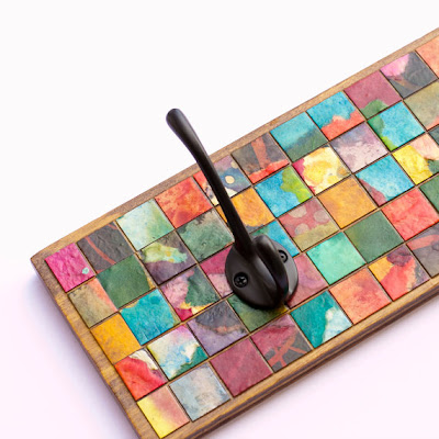 hooks on wood covered with mosaics made from paper