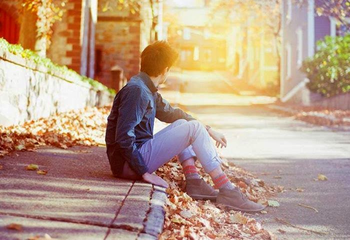 Hình ảnh chàng trai ngồi buồn bên vệ đường