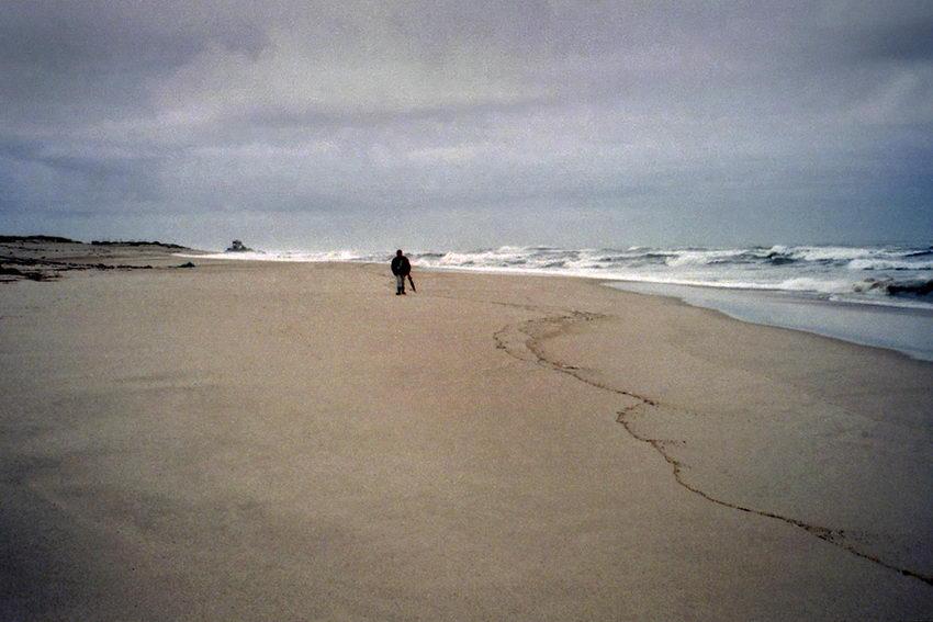 Praia deserta com um home a andar na areia. Ao longe a capela do Senhor da Pedra. Céu encoberto