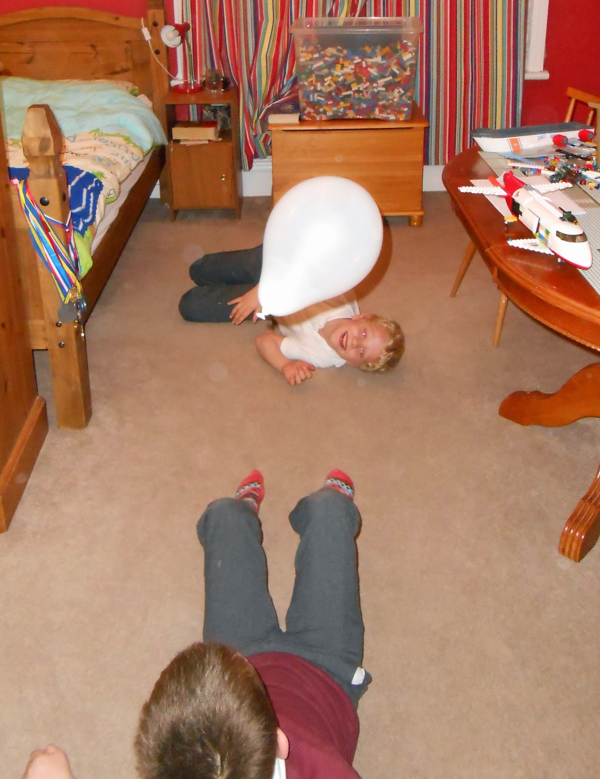 schoolboys on bedroom floorlego table and medals on bedpost