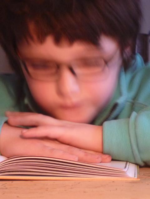 Ein Kind (unscharf) in ein Buch vertieft (scharf)