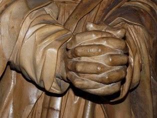 una statua con mani giunte
