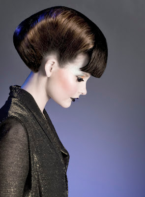 80s inspired hairdressing photoshoot. Model in profile with pale skin and dark lips, Structured hair with a sharp fringe
